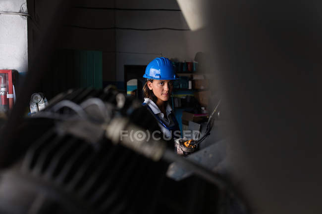 Female mechanic wearing hardhat operating hoist at workshop — Stock Photo