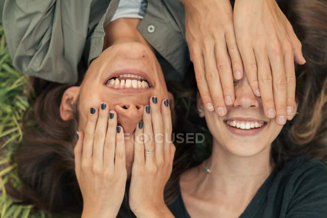 Retrato de casal sorridente deitado na grama e escondendo os rostos uns dos outros  . — Fotografia de Stock