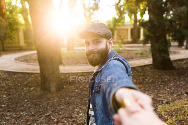 Bearded man in denim jacket and cap holding hand and gesturing Follow me in sunlight. — Stock Photo