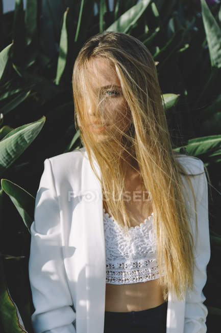 Portrait of blonde woman wearing white top and jacket posing in wind with obscured face — Stock Photo