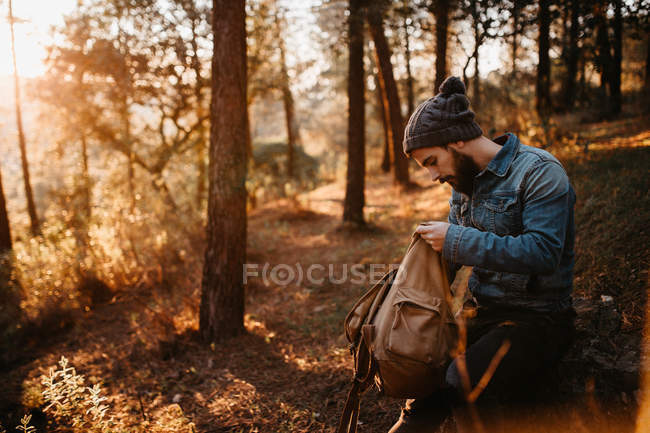 Side view of tourist looking into backpack in autumn forest. — стокове фото