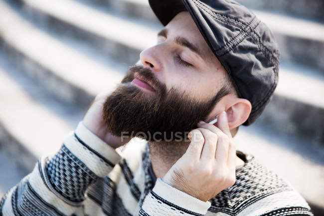 Portrait of bearded man with eyes closed putting earphones to  ears. — Stock Photo