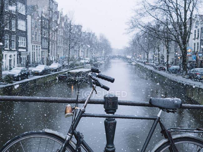 Bicicleta de cultivo estacionada en el puente sobre el canal de la ciudad día nevado - foto de stock