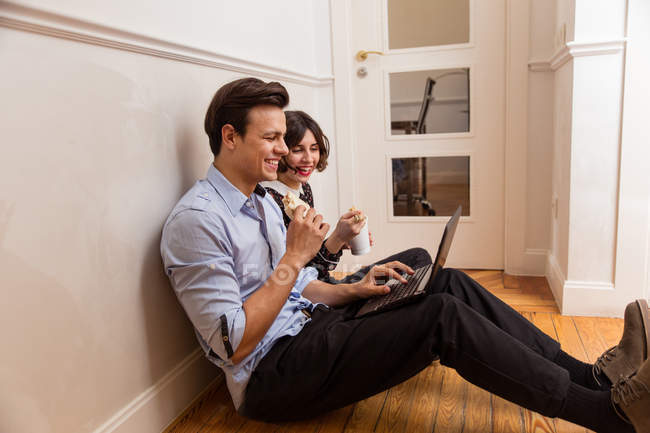 Side view of young cheerful friends in casual wear sitting on floor with laptop while eating wok — Stock Photo
