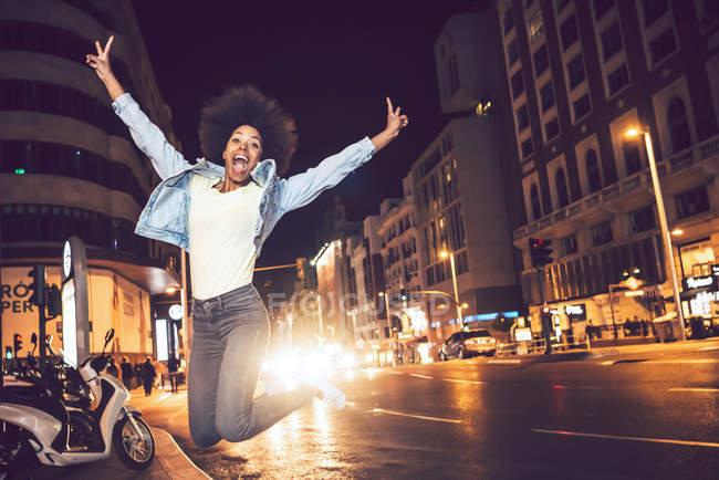 Belle jeune femme noire sautant dans la rue de la ville la nuit — Photo de stock