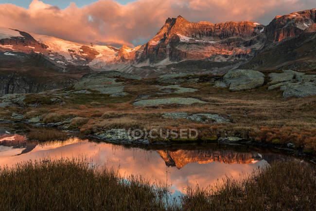 Surface du lac reflétant les montagnes ensoleillées — Photo de stock