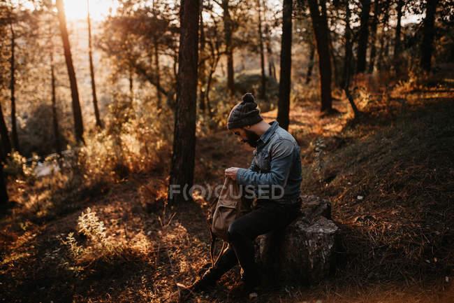 Mann sitzt im Wald und blickt in Rucksack — Stockfoto