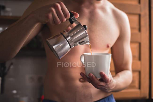 Мидсекция человека без рубашки наливает кофе в белую кружку . — стоковое фото