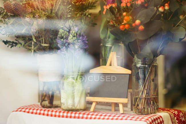 Diferentes ramos de flores naturales en frascos en florería detrás de ventana - foto de stock