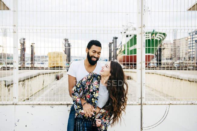 Couple hugging near wharf gates — Stock Photo