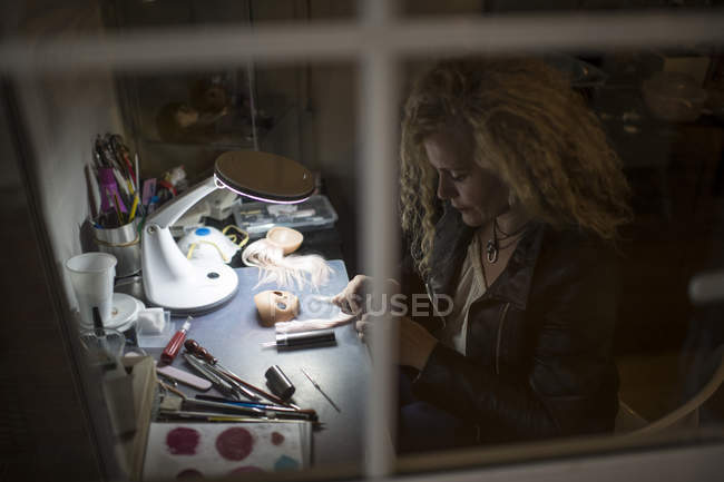 View through window of woman crafting dolls at table — Stock Photo