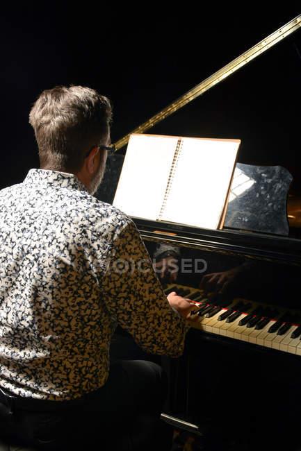 Rückansicht eines älteren Mannes, der Klavier spielt — Stockfoto