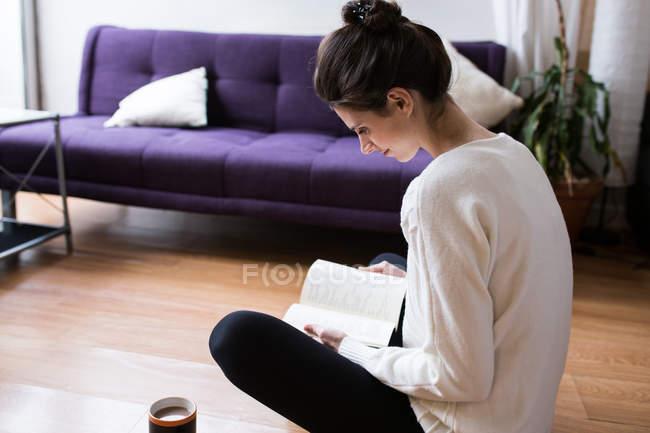 Вид сбоку студентки, сидящей на полу со скрещенными ногами и читающей книжку — стоковое фото