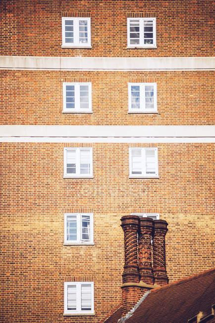 Vista exterior de ladrillo bloque de pisos y chimenea - foto de stock