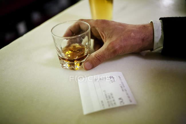 Куст мужской руки, держащий стакан с алкогольным напитком на барной стойке, рядом со счетом . — стоковое фото