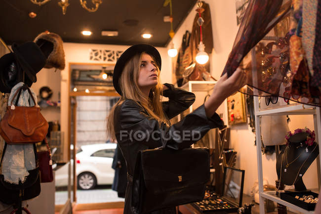Young trendy girl in hat looking for accessories in shop. — Stock Photo