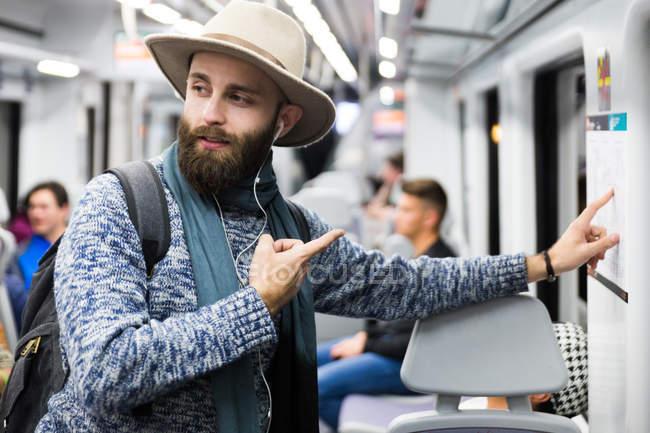 Турист в вагон, указывая на карте метро и глядя с путают лицом — стоковое фото