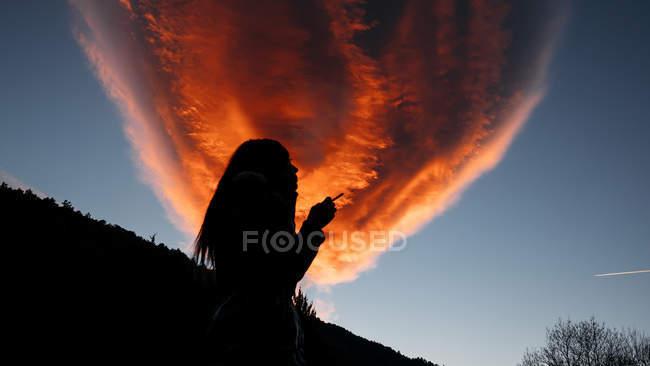 Menina silhueta fumar contra a nuvem vermelha — Fotografia de Stock