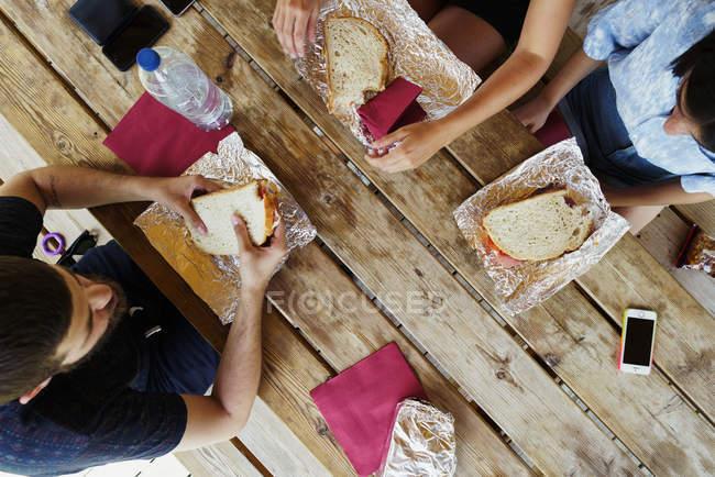 Друзья сидят за деревянным столом и едят — стоковое фото