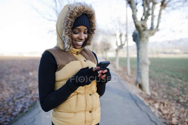 Ragazza sorridente in giacca smartphone di navigazione al parco — Foto stock