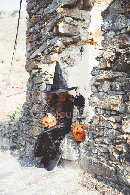 Девушка в костюме Хэллоуина сидит на каменной стене — стоковое фото