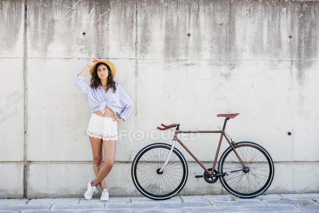 Chica posando cerca de bicicleta - foto de stock
