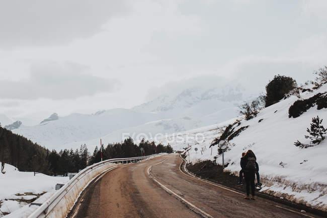 Vista trasera del par caminar espalda alcancía en el camino de invierno en las montañas - foto de stock