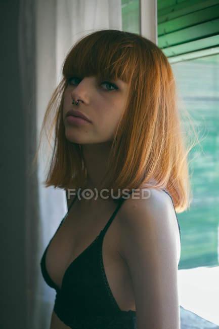 Junges Mädchen in schwarzem BH posiert am Fenster — Stockfoto