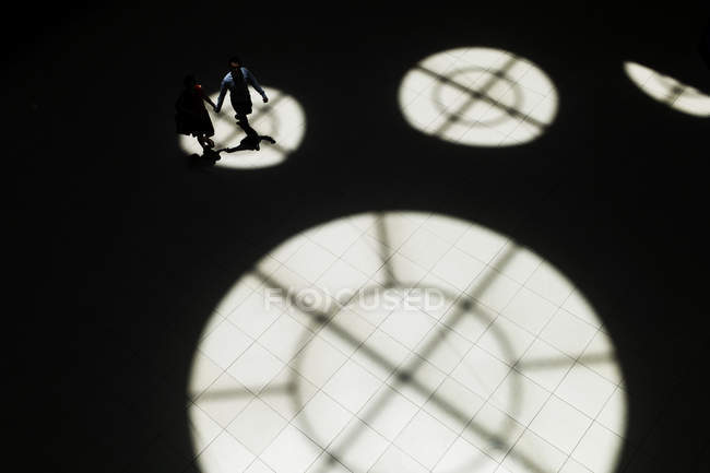 High angle view of anonymous couple holding hands and walking in hall with circle light spots and shadows of windows. — Stock Photo