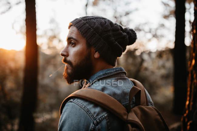 Homem barbudo olhando por cima do ombro em florestas de outono . — Fotografia de Stock