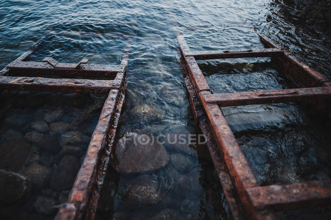Low angle view of iron old rails in clear water — Stock Photo