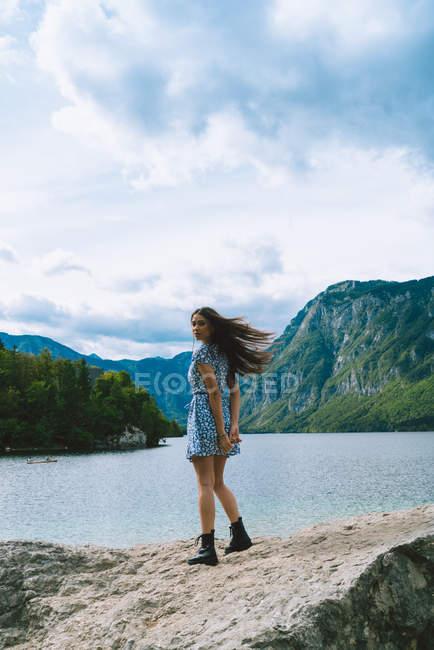 Mulher posando na pedra no lago de montanha — Fotografia de Stock