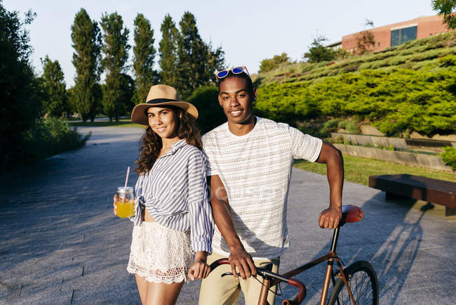 Couple with drinks and bike  posing over urban park — Stock Photo