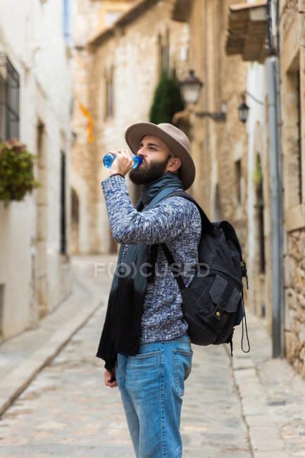 Бородатый мужчина с рюкзаком питьевой воды на улице . — стоковое фото