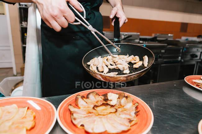Sección media de cocinar la colocación de ingredientes con pinzas en los platos en la cocina del restaurante - foto de stock