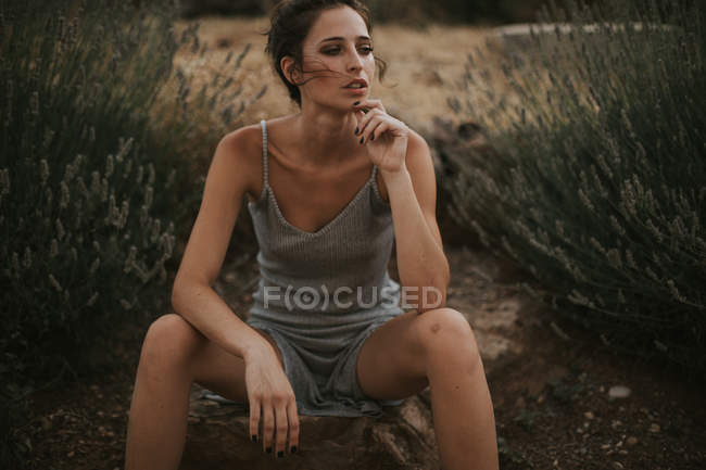 Portrait of woman with windy hair sitting on stone in dress and looking pensively away — Stock Photo