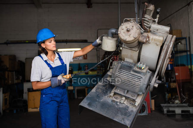 Female mechanic wearing hardhat operating a hoist to lift compressor engine — Stock Photo