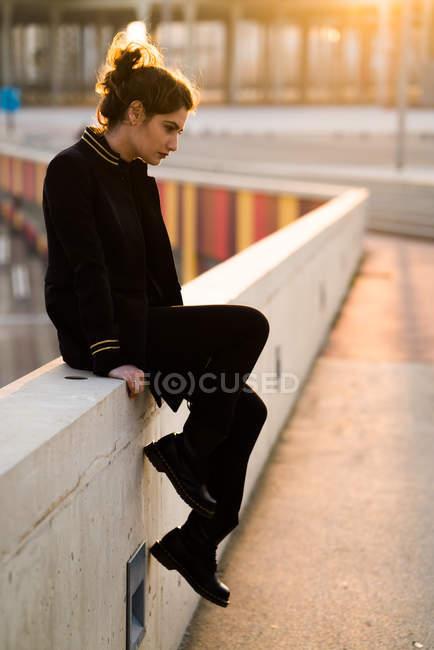 Nachdenkliche Frau sitzt am Geländer und blickt nachdenklich nach unten — Stockfoto