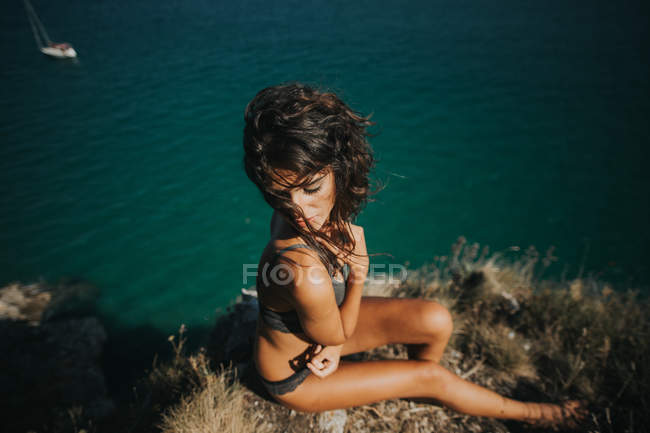 High angle view of brunette woman posing with eyes closed on rock over ocean surface — Stock Photo