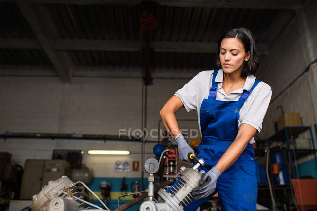 Portrait of brunette female mechanic fixing compressor engine with wrench — Stock Photo