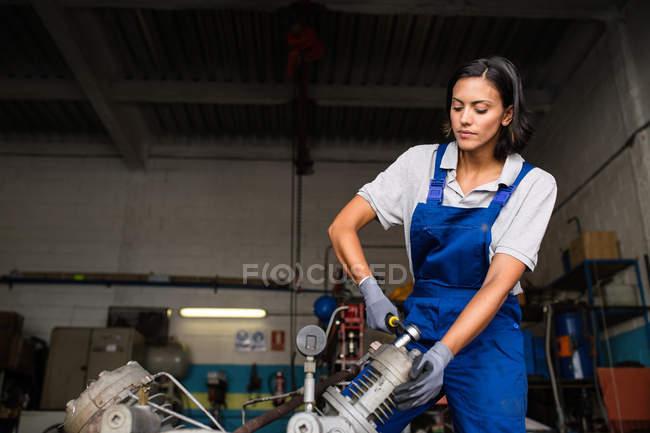Retrato de Morena mujer mecanica motor de compresor fijación con una llave de - foto de stock