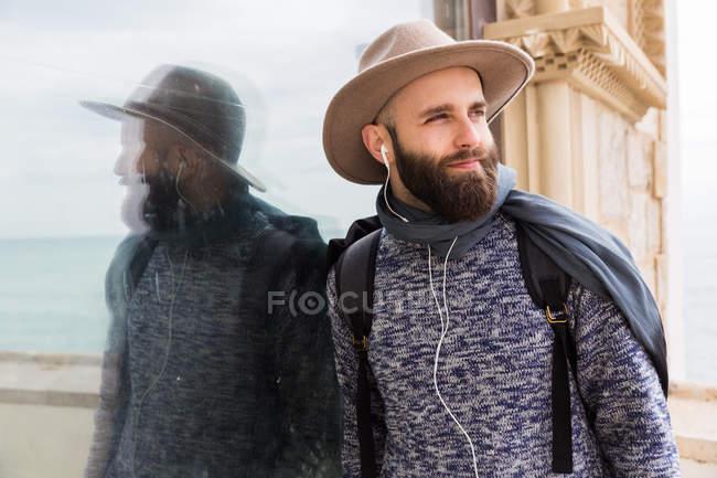 Ritratto di uomo barbuto con gli auricolari appoggiati al vetro e distolti lo sguardo — Foto stock