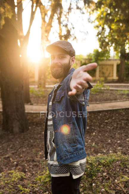 Portrait of bearded man in denim clothing smiling and outstretching hand at camera on background of park in sunlight. — Stock Photo