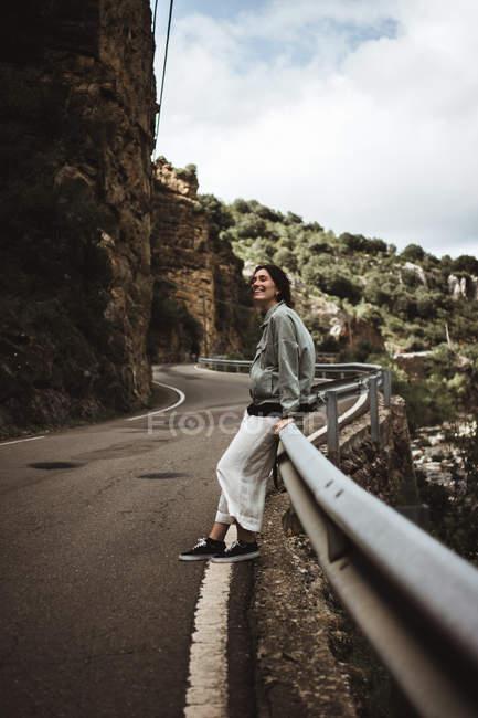Femme joyeuse, se penchant sur la barrière de la route dans les montagnes — Photo de stock