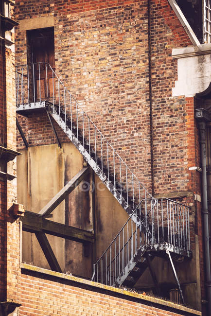 Vista del vecchio edificio in mattoni e la scaletta di fuoco corroso — Foto stock
