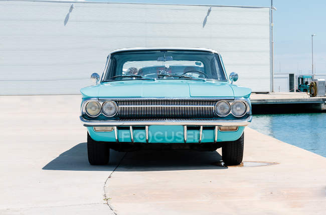 Turquoise vintage car by swimming pool — Stock Photo