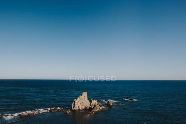 Idilliaco paesaggio marino con rocce contro di cielo azzurro chiaro — Foto stock