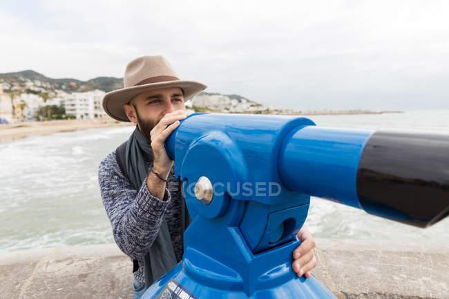 Homem barbudo em pé na costa e apontando com sightseeing máquina binocular — Fotografia de Stock