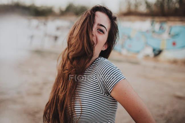 Сміючись дівчина в смугаста Майка, дивлячись на камеру з половину обличчя на пляжі — стокове фото
