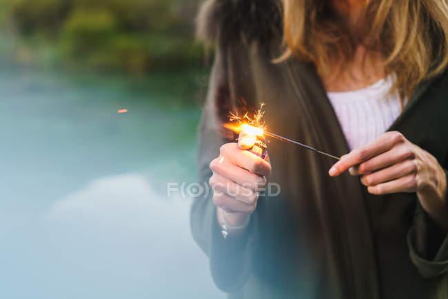 Crop shot of woman holding lighter and lighting festive sparkler . — Stock Photo